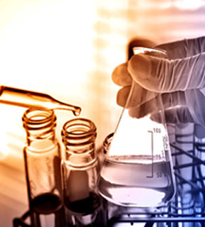 Image of a Chemist handling flask and test tubes